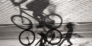 Ciclista y silueta y sombra borrosos del niño Fotos de archivo