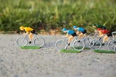 Ciclistas amarelos plásticos da estrada exteriores no asfalto Jérsei amarelo que quebra afastado competição Peloton Imagem de Stock