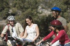 Ciclistas con el mapa itinerario Fotografía de archivo libre de regalías
