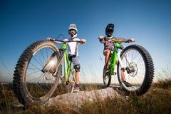 Ciclistas con las bicis de montaña en la colina debajo del cielo azul Fotos de archivo