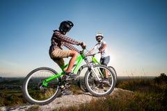 Ciclistas con las bicis de montaña en la colina debajo del cielo azul Fotografía de archivo libre de regalías