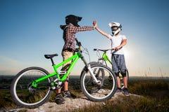 Ciclistas con las bicis de montaña en la colina debajo del cielo azul Imagenes de archivo