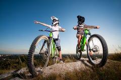 Ciclistas con las bicis de montaña en la colina debajo del cielo azul Fotografía de archivo