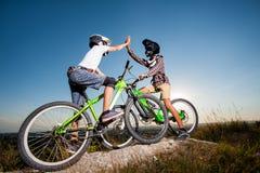 Ciclistas con las bicis de montaña en la colina debajo del cielo azul Foto de archivo libre de regalías