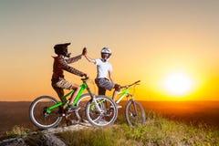 Ciclistas con las bicis de montaña en la colina por la tarde Fotografía de archivo