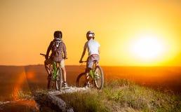 Ciclistas con las bicis de montaña en la colina por la tarde Imagenes de archivo