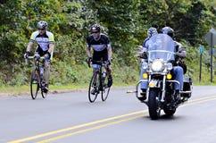 Ciclistas e uma motocicleta na estrada Fotografia de Stock Royalty Free