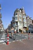 Ciclistas en el centro de ciudad soleado, Amsterdam, Países Bajos Foto de archivo