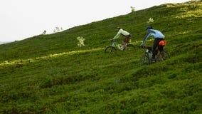 Ciclistas en la manera abajo en las montañas Imagen de archivo libre de regalías