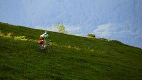 Ciclistas en la manera abajo en las montañas Imagenes de archivo