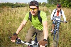 Ciclistas en prado Foto de archivo libre de regalías
