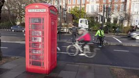 Ciclistas en un carril del ciclo ir más allá de una caja británica del teléfono bajo la lluvia almacen de metraje de vídeo