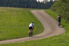 ciclistas en una opinión de la distancia sobre un día soleado del verano fotografía de archivo