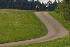 ciclistas en una opinión de la distancia sobre un día soleado del verano fotos de archivo libres de regalías