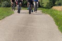 ciclistas en una opinión de la distancia sobre un día soleado del verano imágenes de archivo libres de regalías