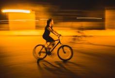 Ciclistas felices que montan las bicis en una ciudad Foto de archivo libre de regalías