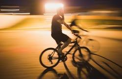 Ciclistas felices que montan las bicis en una ciudad Imagenes de archivo