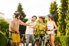 Ciclistas jovenes que juegan el roca-tijera-papel al aire libre imagen de archivo libre de regalías