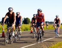 Ciclistas que compiten con en medio acontecimiento ironman. Fotos de archivo