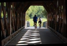 Ciclistas que cruzan el puente cubierto, Guelph Imágenes de archivo libres de regalías