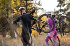 Ciclistas que levam bicicletas imagem de stock