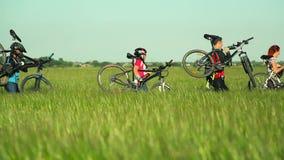 Ciclistas que levam bicicletas através da grama alta video estoque