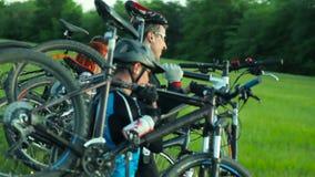 Ciclistas que levam bicicletas através da grama alta vídeos de arquivo