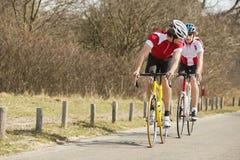 Ciclistas que montam na estrada secundária Imagens de Stock