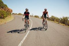 Ciclistas que montan abajo de una carretera nacional Imagenes de archivo
