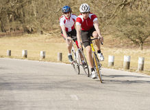 Ciclistas que montan en una carretera nacional Imagen de archivo libre de regalías