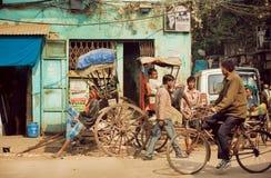 Ciclistas y peatones en la calle muy transitada de la ciudad india en el día soleado Foto de archivo