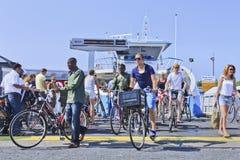Ciclistas y peatones en llegada del transbordador, Amsterdam Fotografía de archivo libre de regalías