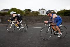 Ciclisti, facenti una panoramica della tecnica, secondo flash di sincronizzazione della tenda Fotografia Stock