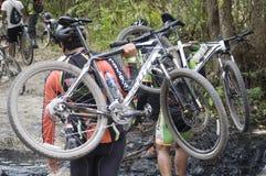 Ciclisti in mountain-bike che attraversano fango fotografia stock libera da diritti