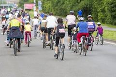 Ciclisti nel traffico sulle vie immagini stock