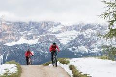 Ciclisti sui mountain bike su una pista con nei precedenti le montagne che fa parte di Th fotografie stock libere da diritti