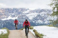 Ciclisti sui mountain bike su una pista con nei precedenti le montagne che fa parte di Th fotografia stock libera da diritti