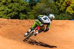Ciclo de BMX que compite con la esquina masculina Imagen de archivo libre de regalías