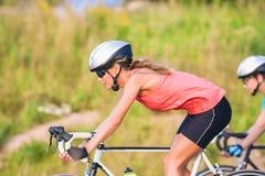 Ciclo de treinamento dos dois desportistas caucasianos fêmeas que montam s Foto de Stock Royalty Free