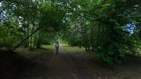 Ciclo en el parque Muchacha que monta una bici en un rastro del bosque Cámara lenta metrajes