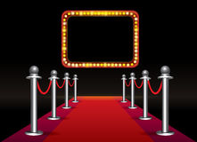 Ciclo magico del tappeto rosso con l'insegna con le lampadine su fondo nero Fotografia Stock