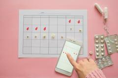 Ciclo menstrual Calend?rio para o m?s com marcas e uma aplica??o m?vel na tela do smartphone imagens de stock royalty free