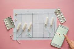 Ciclo menstrual Calend?rio para o m?s com marcas e uma aplica??o m?vel na tela do smartphone fotos de stock royalty free