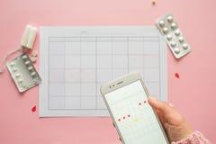 Ciclo menstrual Calend?rio para o m?s com marcas e uma aplica??o m?vel na tela do smartphone fotografia de stock royalty free