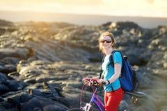 Ciclo turístico joven en campo de lava en Hawaii Caminante femenino que dirige al área de visión de la lava en Kalapana en su bic Foto de archivo