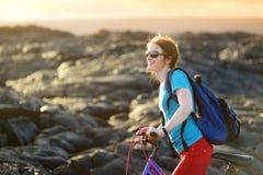 Ciclo turístico joven en campo de lava en Hawaii Caminante femenino que dirige al área de visión de la lava en Kalapana en su bic Fotografía de archivo