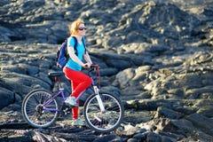 Ciclo turístico joven en campo de lava en Hawaii Caminante femenino que dirige al área de visión de la lava en Kalapana en su bic Imágenes de archivo libres de regalías