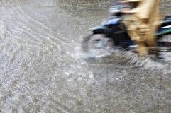Ciclomotor móvil en una calle de la lluvia Fotografía de archivo libre de regalías