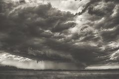 Ciclone da tempestade do verão sobre montes do campo e a nuvem chuvosa pesada assustador assustador grande da floresta sobre a fo imagem de stock