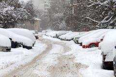 Ciclone do inverno Ruas Uncleaned com os montes de neve pesados após a queda de neve na cidade, carros sob a neve Estradas gelada Fotos de Stock Royalty Free